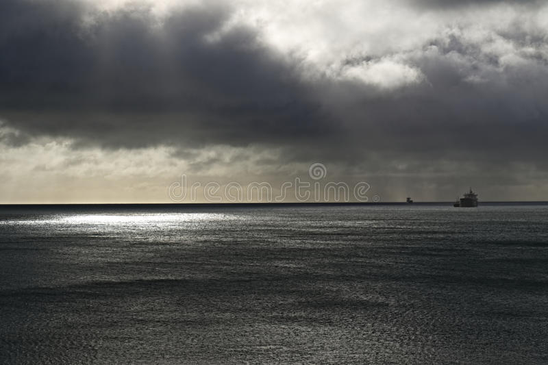 Dark Sky at Sea. Ships shelter from approaching storm, dark clouds and rain stock image