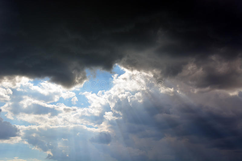 Dark sky with sun rays through the clouds, black blue and white royalty free stock photos