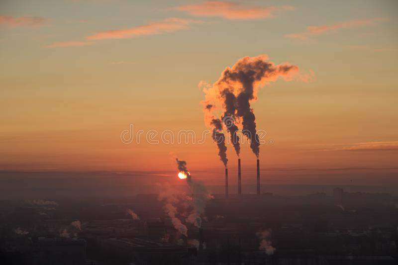 Dark smoke coming from the thermal power plant pipe. Factory smoke, polluting the atmosphere. Industrial zone in the city royalty free stock image