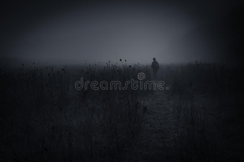 Dark spooky landscape with lonely man walking on field stock photos