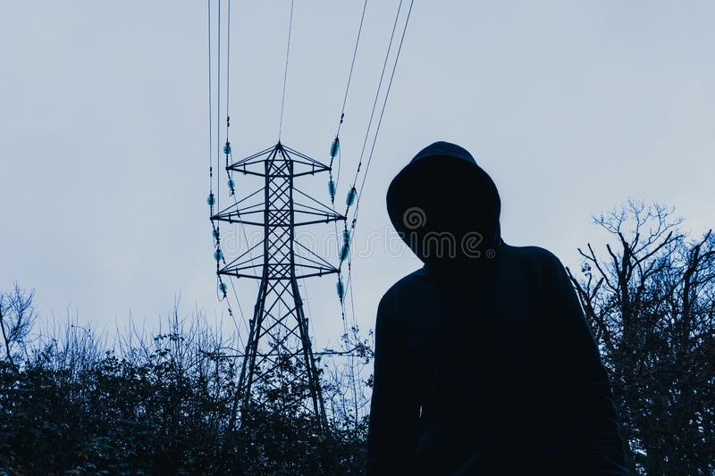 A dark spooky, moody edit. A hooded figure looking at the camera below an energy electricity pylon on a winters evening in the stock image