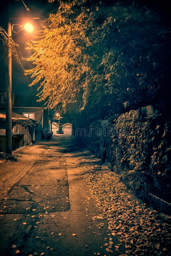 Dark and spooky vintage downtown urban city street alley at night royalty free stock photography