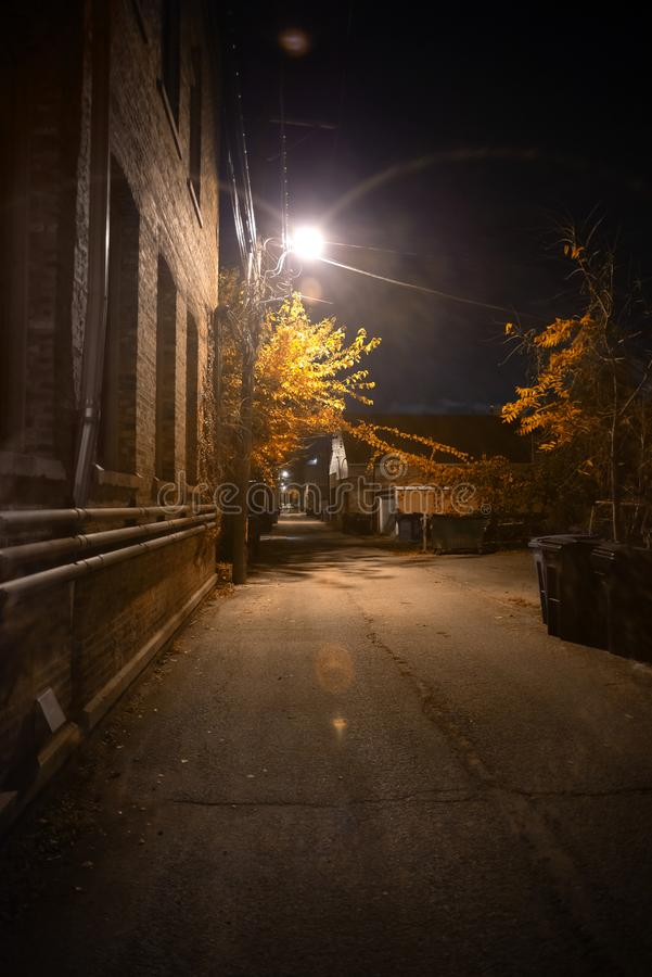 Dark and spooky vintage downtown urban city street alley at night royalty free stock images