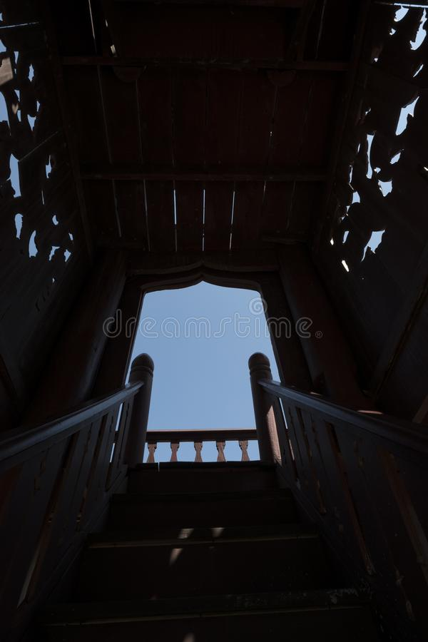 Dark stairs and walkway up to the sky. Wooden stair to step up to opening sky. Low angle of Broken wooden stairs to the balcony with sky stock photo