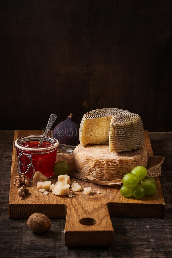 Dark still life with cheese board, fruits and wine. On the rough wooden background royalty free stock photography