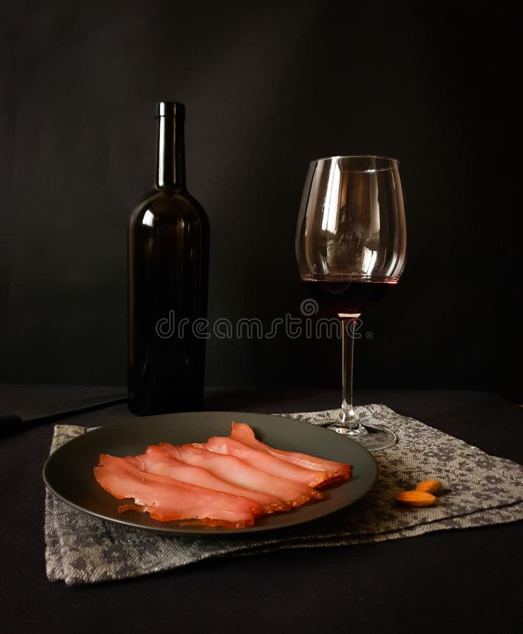 Dark still life. Black bottle of wine, a glass with red wine and a black plate with dried meat on a decorative ornamental napkin on a black background. red royalty free stock image