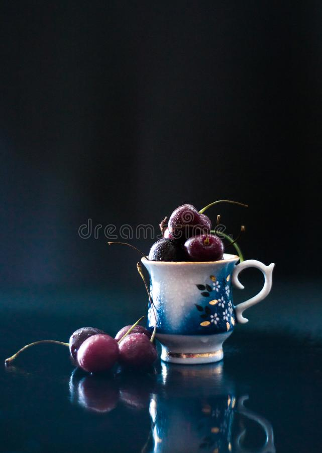 Dark still life with porcelain cup of fresh cherries stock image