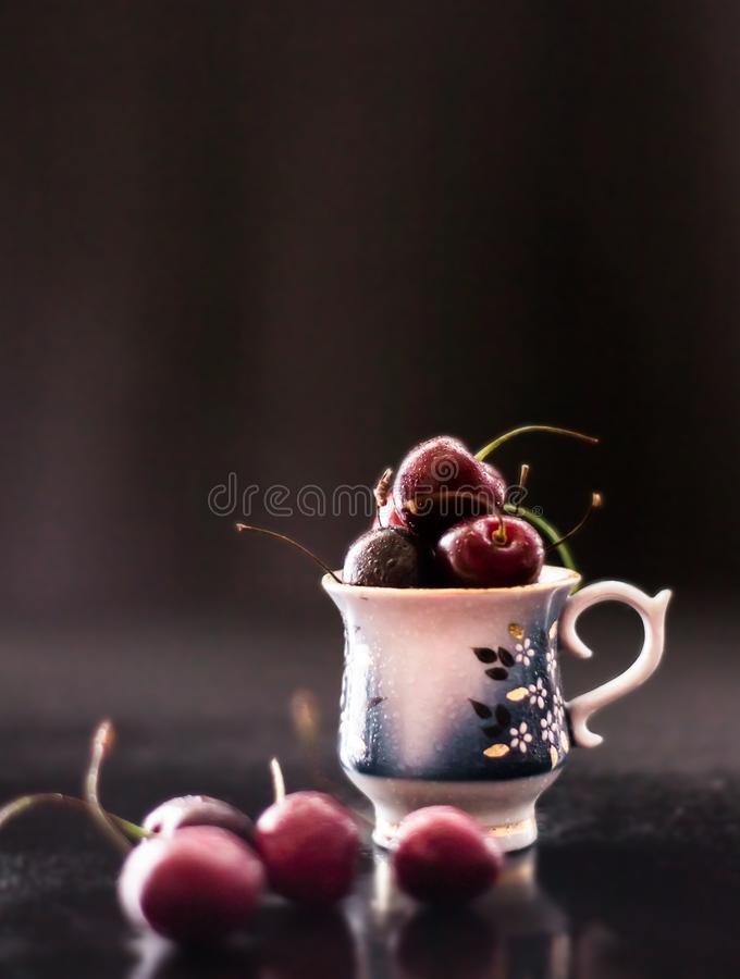 Dark still life with porcelain cup of fresh cherries stock photography