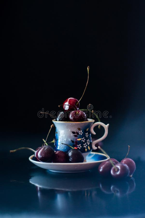Dark still life with porcelain cup of fresh cherries royalty free stock image