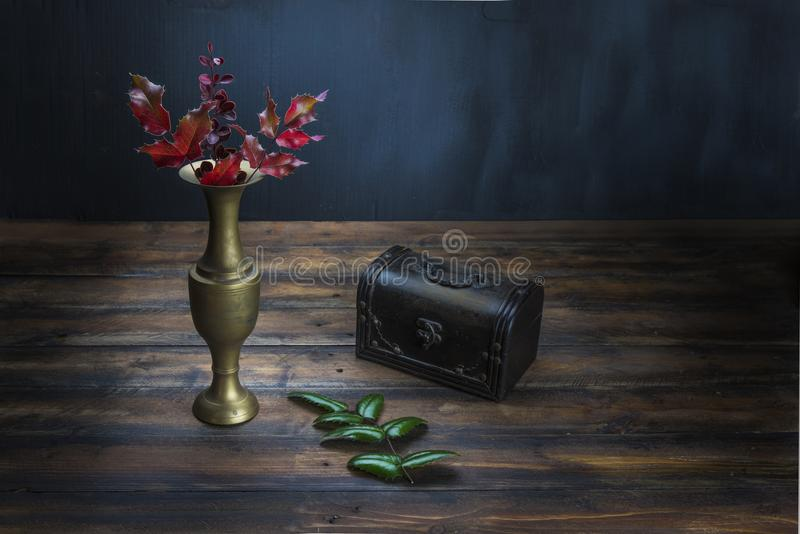 Dark still life with vase and flowers. royalty free stock photography