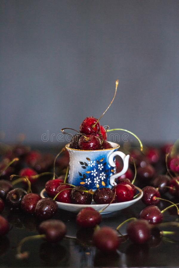 Dark stillife with porcelain cup of fresh cherries. Dark stillife with porcelain cup of cherries with water drops royalty free stock photos