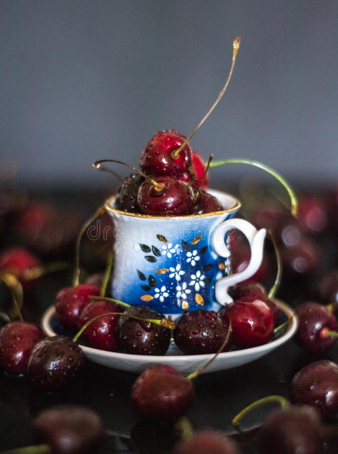 Dark stillife with porcelain cup of fresh cherries stock images