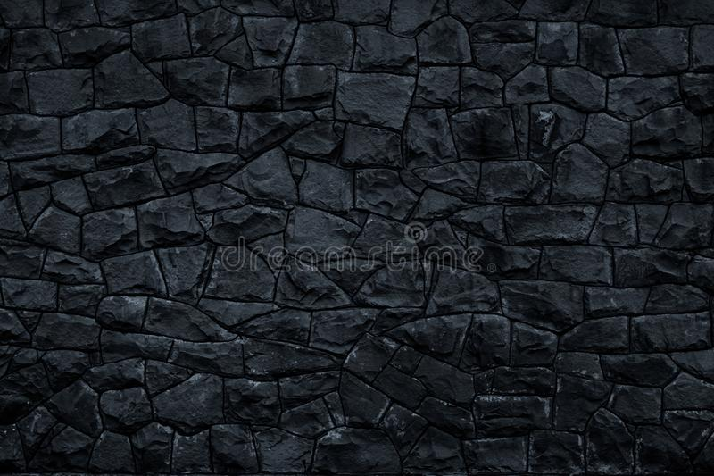 Dark stone background. Black rock wall texture. Abstract pattern. Natural backdrop. Decoration gray tiles at the facade of the bui stock photography