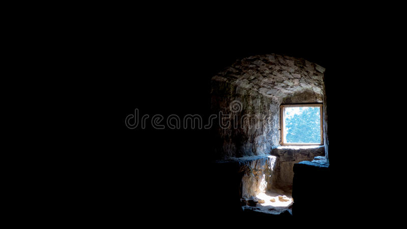 Light at the end of tunnel. Concept. Dark medieval room with light going through the window stock image
