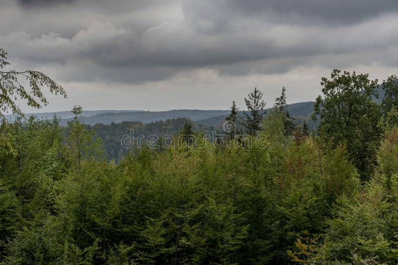 Dark storm clouds over the mixed forest trees stock photography