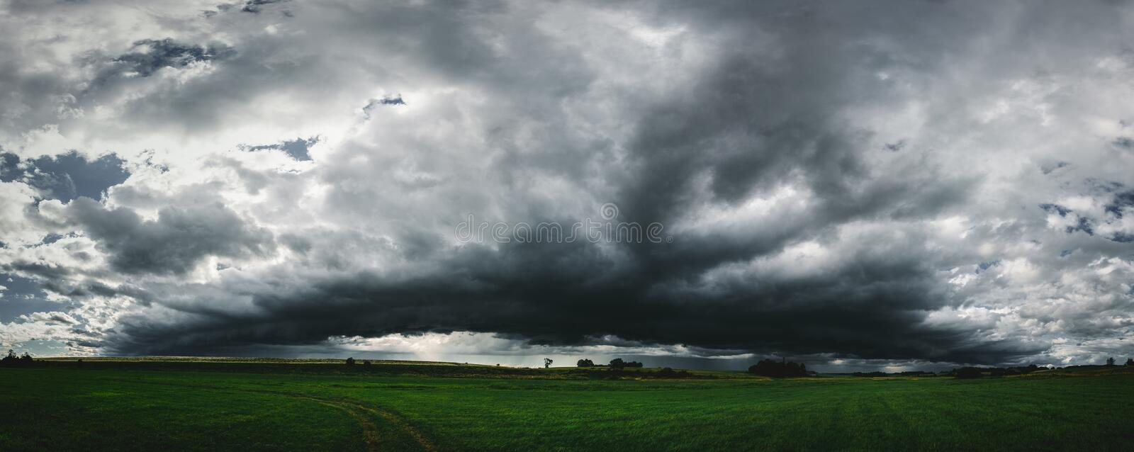 Dark storm clouds panorama above the green grass field stock photo