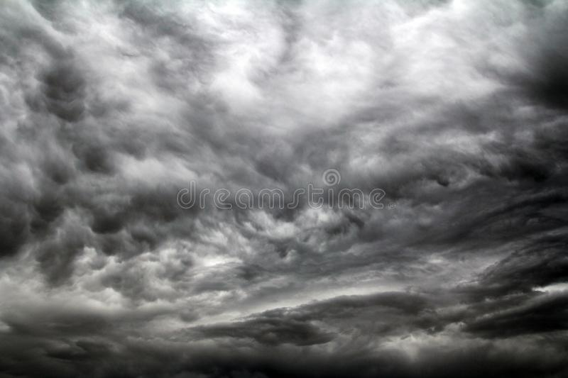 In the sky dark clouds form before a storm. Dark storm clouds in the sky. In the sky dark clouds form before a storm royalty free stock photo
