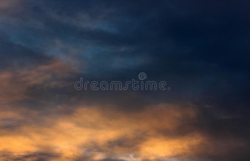 Dark stormy background of clouds and blue skies ready for the thunder and lightning. Dark, stormy clouds overhead, with combination of sun, blue skies and threat royalty free stock photography