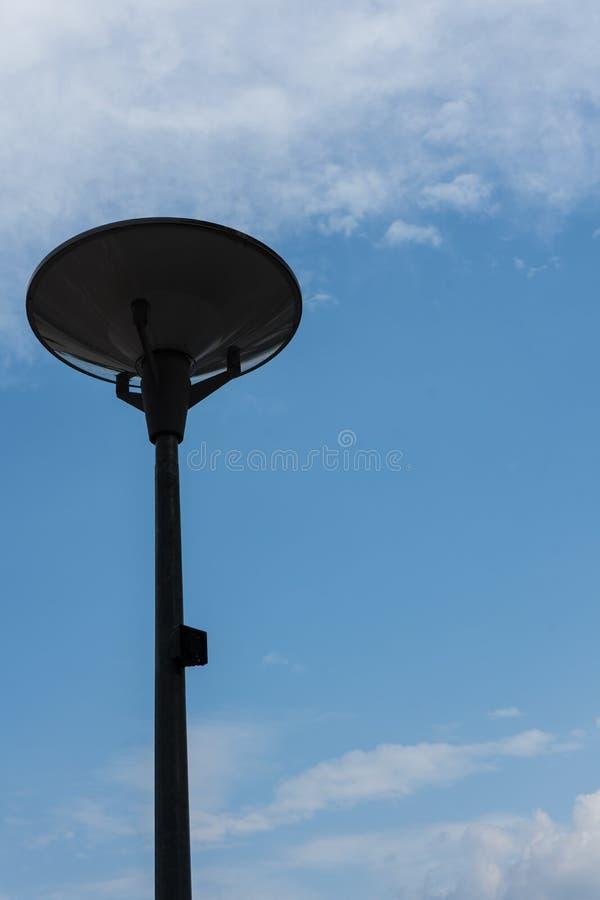 Dark street light isolated with cloudy blue sky stock photos