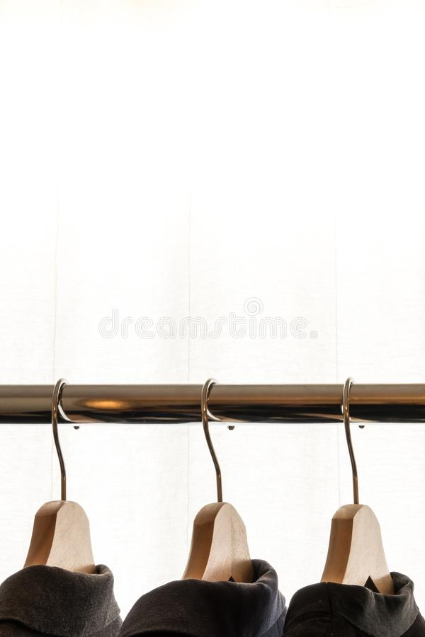 Dark suit jackets on hangers in front of a white background. In a dressing room / walk in closet. Plenty of space for your own text / copy space. Vertical royalty free stock image