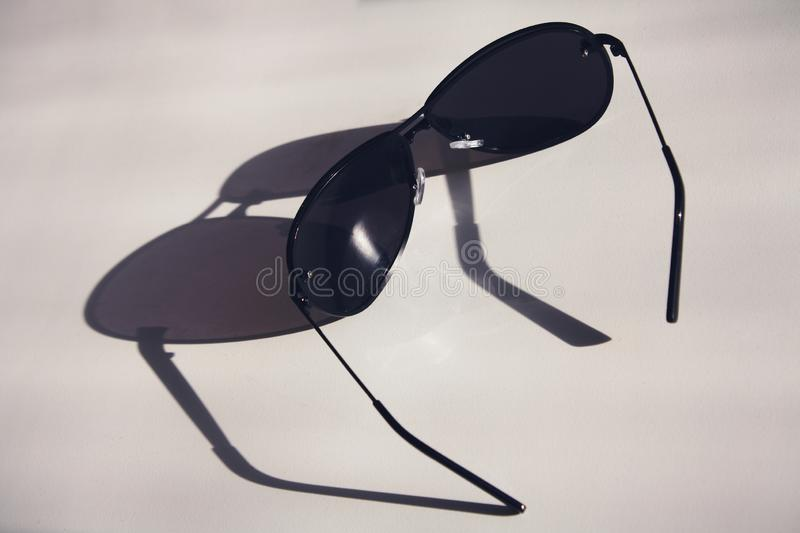 Dark sunglasses lie on a white table, with long shadows, concept royalty free stock image