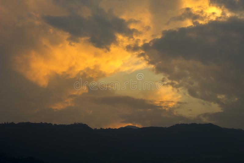 A dark sunset sky with bright orange clouds against the black silhouettes of the mountains. mountain sunset. mountain dawn royalty free stock photos