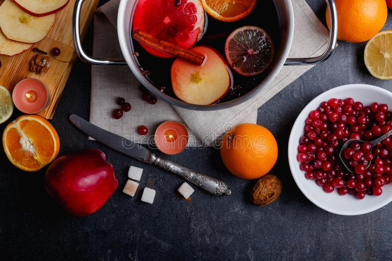On a table is knife, a pot of mulled wine with orange, lemon, apples and cinnamon and cranberries. View from above. On a dark table is a table knife, a pot of royalty free stock photo