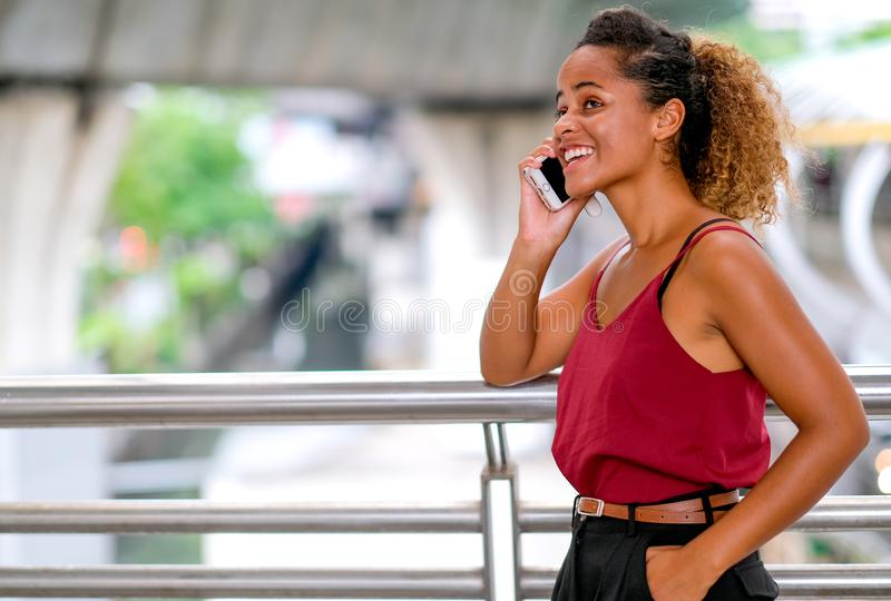 Dark tan skin mixed race woman with smiling call to someone and talk with her mobile phone, also stand the walk way of sky train stock photo