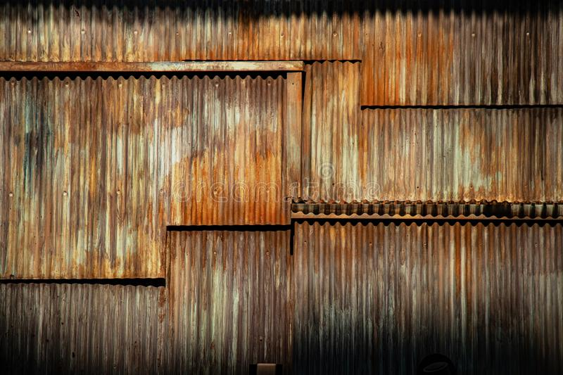 Dark texture corrugated metal background, surface of the rusted steel, slum wall decayed area. Dark grunge texture corrugated metal background, surface of the royalty free stock images