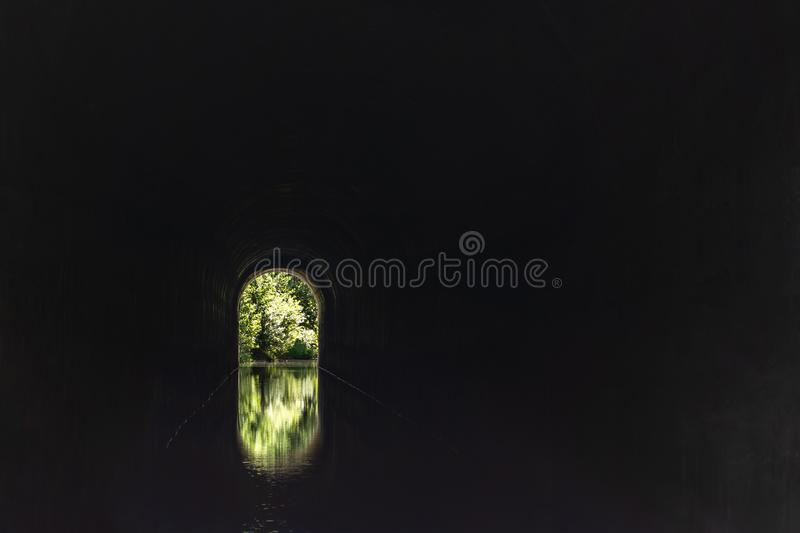 A dark tunnel leading to light. Symbol of the way to heaven after death, clinical death, escape, exit, freedom, psychedelic vision stock photo