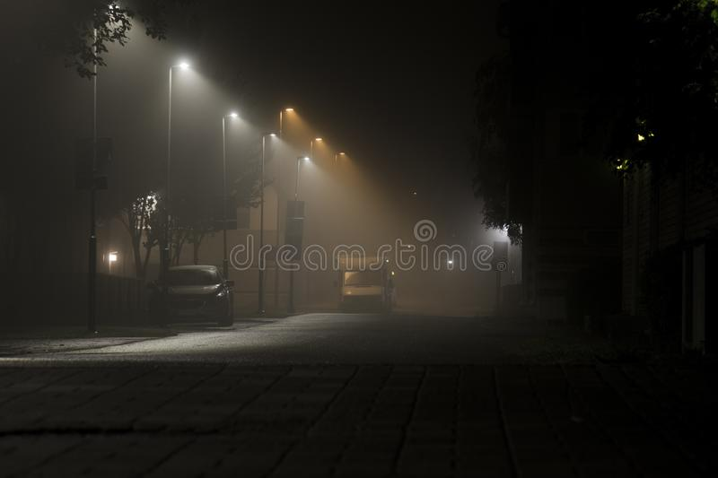 Dark urban city alley at midnight with cars royalty free stock photography