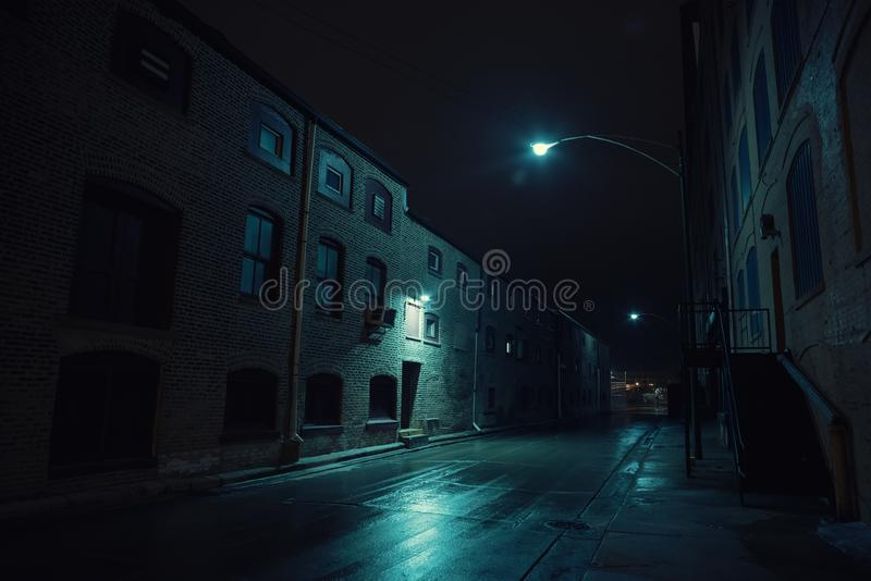 Dark urban city alley at night after a rain. Dark urban city alley at night after a rain featuring vintage warehouses royalty free stock images