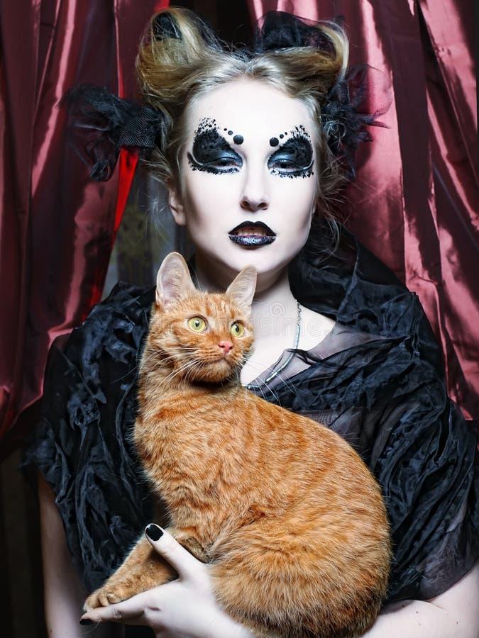 Dark vampire woman with cat. Dark vampire woman with red cat royalty free stock photo