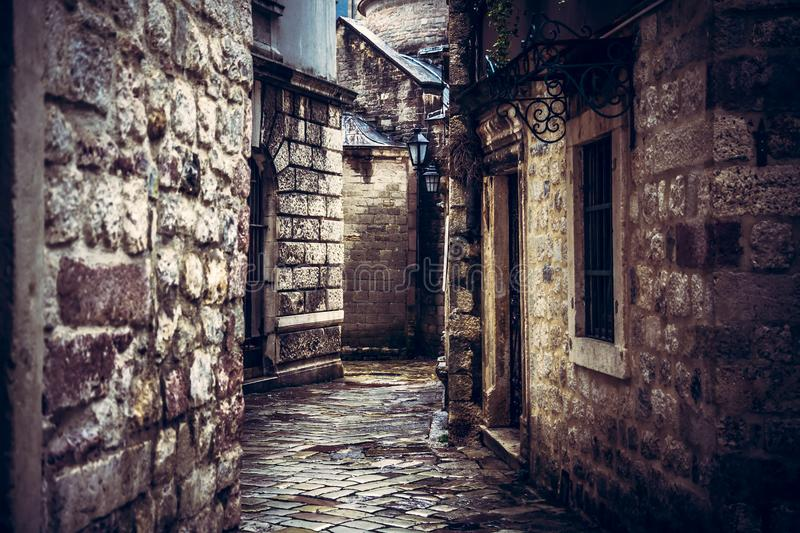 Dark vintage medieval narrow winding street with ancient stone building facade with medieval architecture in old european city Kot. Moody vintage medieval narrow stock photo