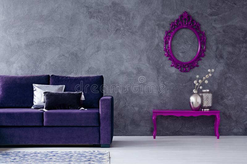 Dark violet living room interior. Mockup on concrete wall in dark living room interior with violet sofa and silver vase on table stock photo
