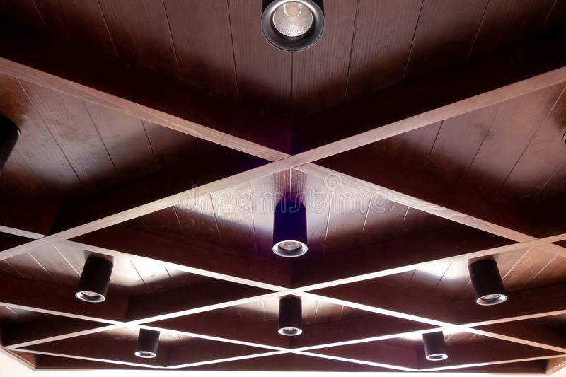 Dark walnut wooden coffered ceiling and modern LED lights royalty free stock image