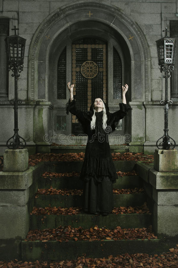 Dark witch is raising her arms to the sky royalty free stock images