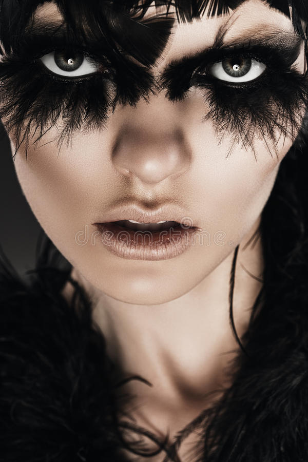 Dark woman with black feathers on eyes. In studio royalty free stock photos