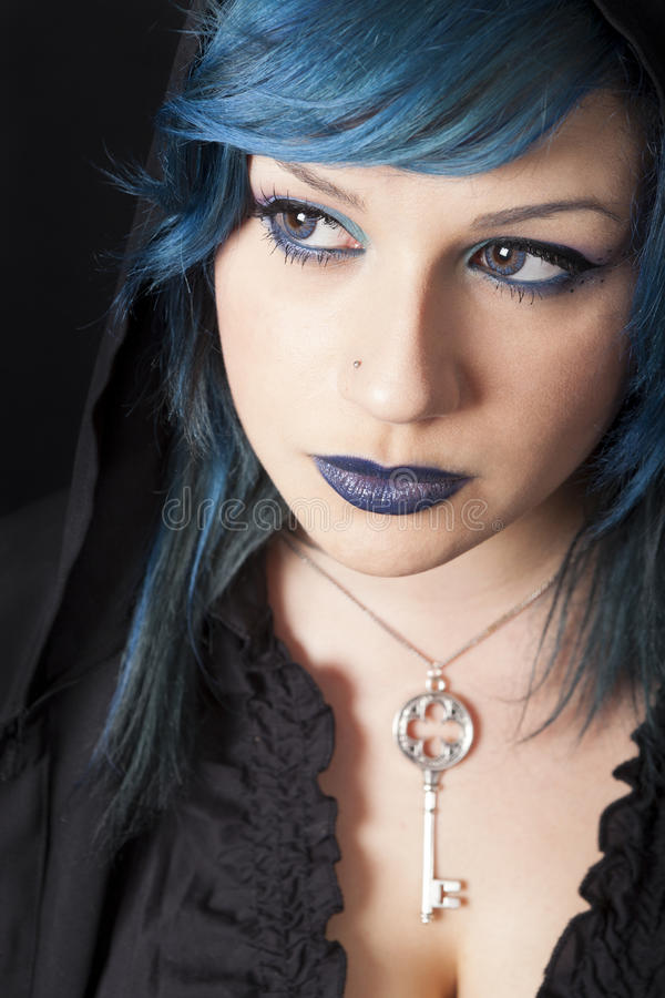 Dark woman with blue hair and lipstick. Key pendant. Dark girl stock photography