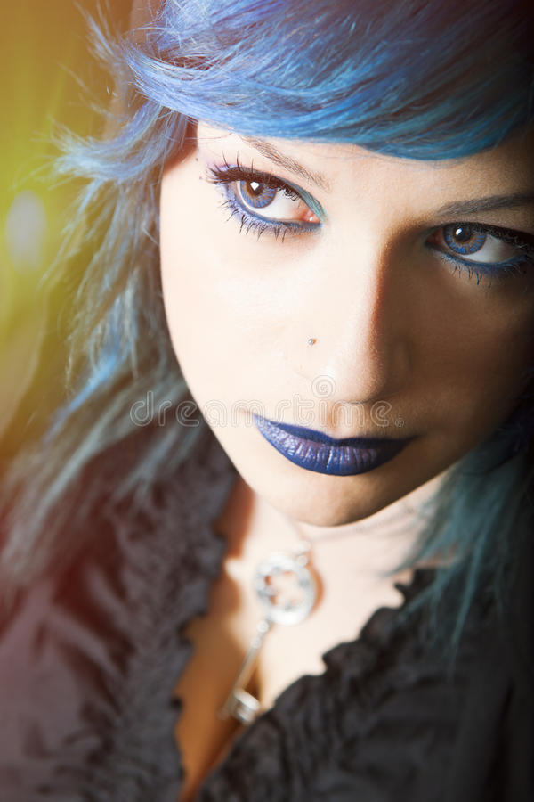 Dark woman with blue hair and lipstick. Key pendant. Dark girl royalty free stock photography