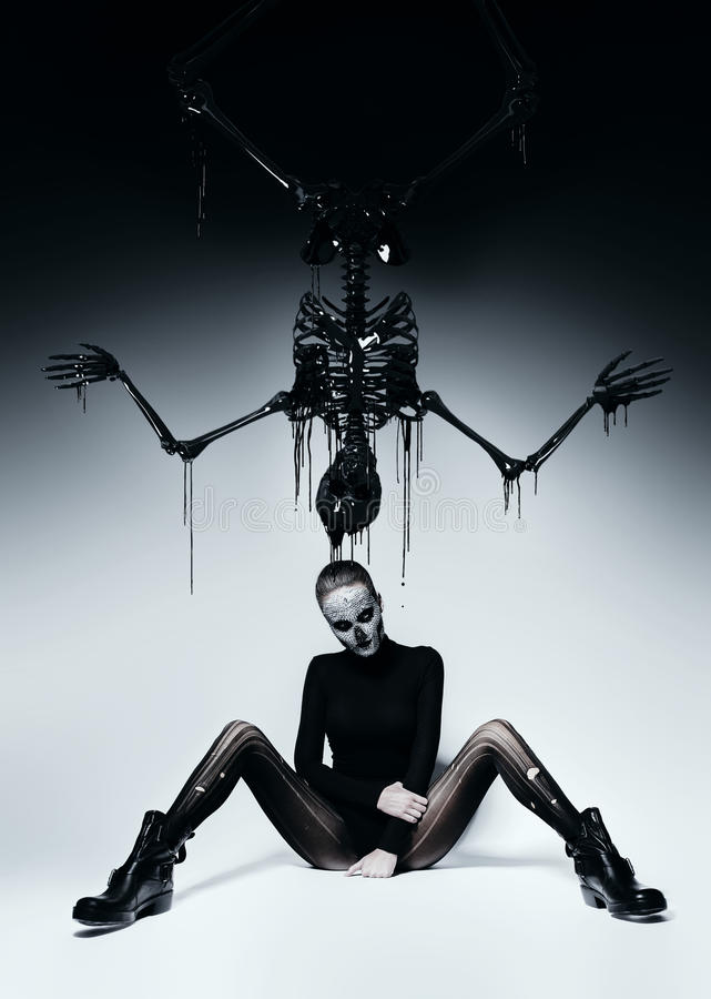 Dark woman with skull face and black skeleton royalty free stock photos