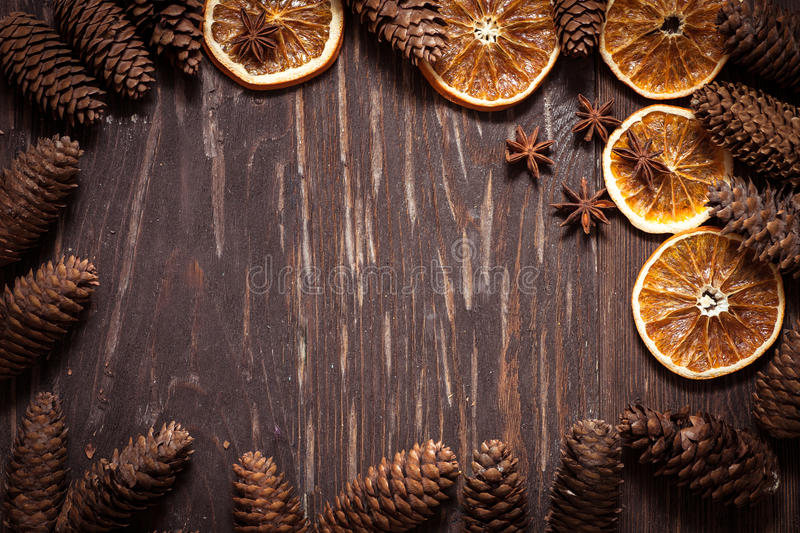 Dark wood background with cones, star anise, dry orange with co. Dark wood background with cones,star anise, and dry orange , with copy space for text, Rustic royalty free stock images