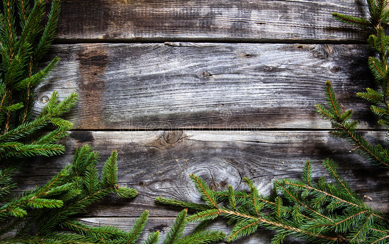 Dark wood background with fir twigs for natural winter frame. Genuine dark wood background with fir tree and twigs for natural winter frame with traditional royalty free stock images