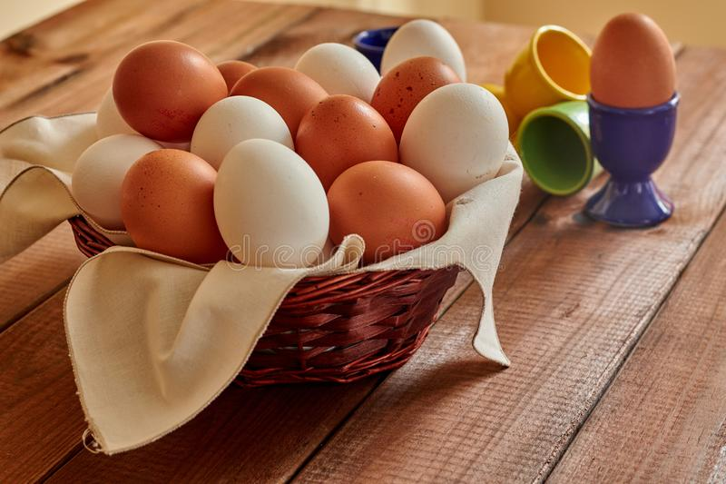 Eggs in wicker basket and egg cups on table stock images