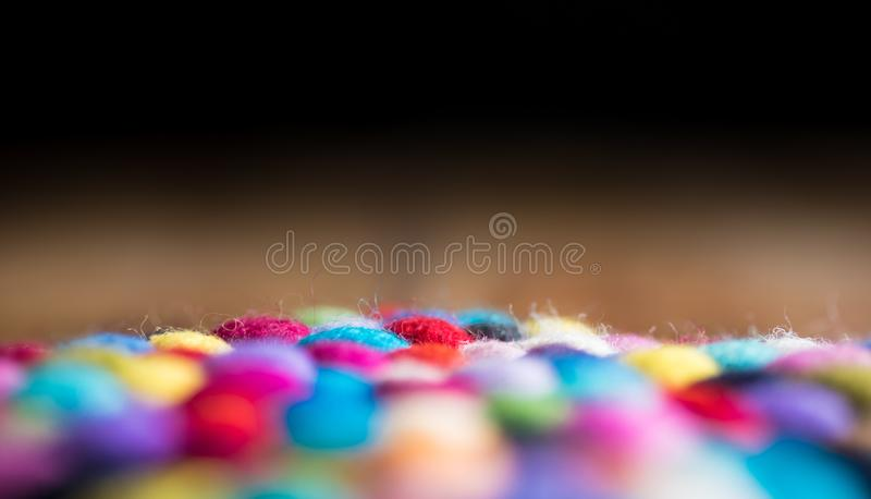 Dark wooden background and colourful fluffy wool balls royalty free stock image