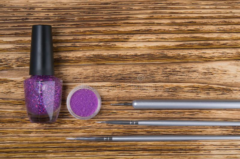 On a dark wooden background, manicure items, purple rhinestones for nails, nail Polish and brushes for easy application, close-up. There is a place for the royalty free stock photography