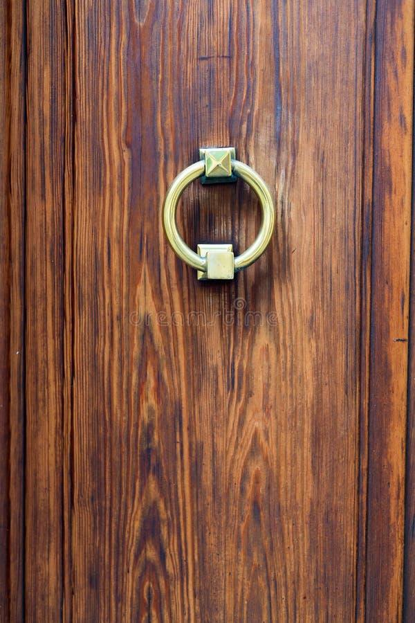Dark wooden door with old bronze handle close up stock images