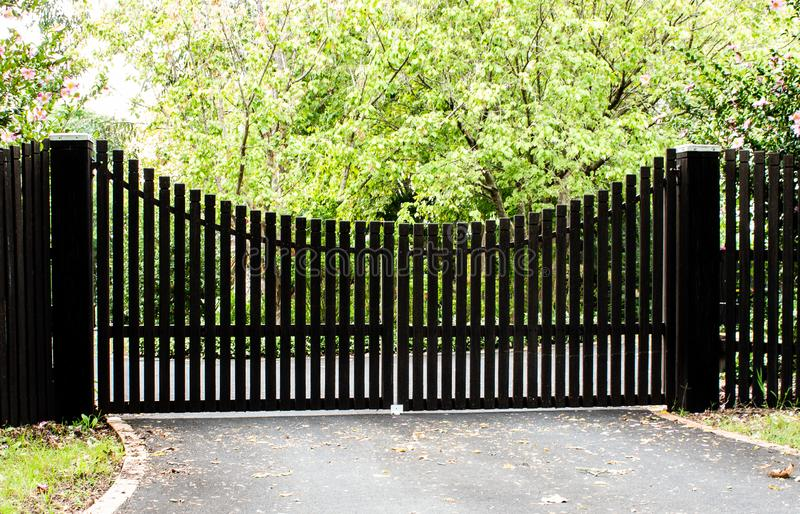 Dark wooden driveway property entrance gates set in timber picket fence with garden shrubs and trees in background. Dark brown wooden driveway property entrance stock photo