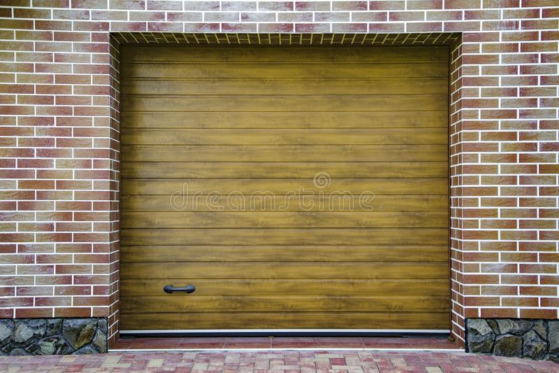 Dark Wooden Garage Door with colored brick wall background. Dark Wooden Garage Door with colored brick wall royalty free stock photos