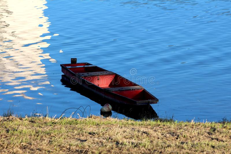 Dark wooden river boat with red center tied to river bank floating on calm clear blue water stock images